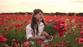 Little smiling girl with bouquet of red poppies standing in flowered field at sunset. Close up stock footage