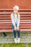 Little smiling girl in a cap sits on bench Stock Photo