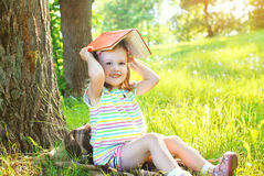 Little smiling girl child with book playing on the grass Royalty Free Stock Photo