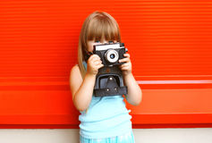 Little smiling girl child with old retro vintage camera Stock Photo