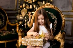 Little smiling girl with christmas gift box. Royalty Free Stock Photos