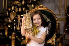 Little smiling girl with christmas gift box. Royalty Free Stock Images