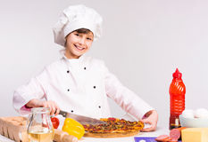 Little smiling girl-cook with big pizza in hands Stock Image