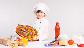 Little smiling girl-cook with big pizza in hands Stock Photography