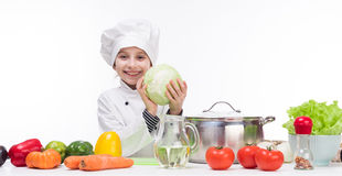 Little smiling girl-cook with cabbage in hands Royalty Free Stock Images