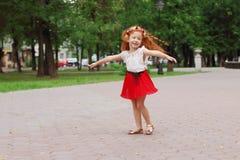 Little smiling girl dances in green summer park, s. Little smiling girl with red hair dances in green summer park, shallow dof Stock Photos