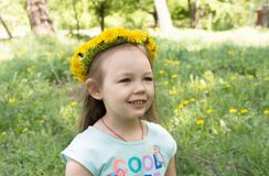 Little smiling girl with dandelion wreath on head.  Stock Photo
