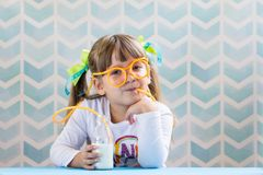 Little smiling girl drinking milk with funny glasses straw stock photo