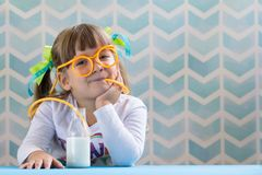 Little smiling girl drinking milk with funny glasses straw royalty free stock photo