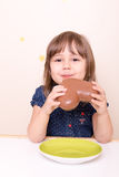 Little smiling girl eating chocolate heart. Little girl eating chocolate heart Royalty Free Stock Photography