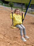 A little smiling girl enjoying swinging in a playground of an apartment house`s court yard stock photos
