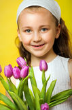 Little smiling girl with flowers. Smiling beautiful young girl with tulips at spring Royalty Free Stock Image