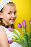 Little smiling girl with flowers. Smiling beautiful young girl with tulips at spring Stock Photos