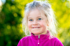 Little smiling girl in front of nature background Royalty Free Stock Images
