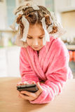 Little smiling girl with hair curlers on her head Stock Photography