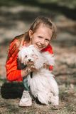 Little girl with a white puppy. A puppy in the hands of a girl. Little smiling girl having fun with puppy outdoors in the park royalty free stock image