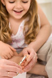 Little smiling girl having her toe nail cut. Personal grooming - woman hands cutting little girl toe nails Stock Photography