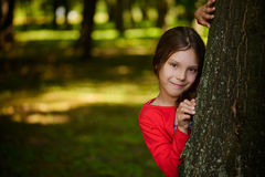 Little smiling girl is hiding behind tree Royalty Free Stock Image