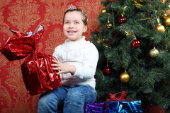 Little smiling girl holds gift near Christmas tree Royalty Free Stock Photos
