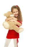 Little smiling girl is hugging with bear red dress Royalty Free Stock Photos