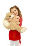 Little smiling girl is hugging  bear in red dress Stock Photo