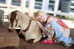 Little smiling  girl hugging the  goat Stock Photo