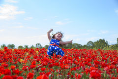 Little smiling girl jumping in flowers field. Portrait of cheerful girl in dress jumping in red flowers field Royalty Free Stock Images