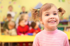 Little smiling girl in kindergarten stock images