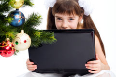 Little smiling girl with laptop computer. By a Christmas tree Royalty Free Stock Image