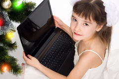 Little smiling girl with laptop computer. By a Christmas tree Stock Photography
