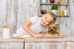 Little smiling girl is leaning down to her pet. Stock Photos