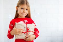 Smiling girl holding Christmas gift royalty free stock photos