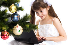 Little smiling girl looks at her laptop computer Stock Photography