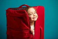 Little smiling girl looks out of red suitcase, portrait of cheerful child on blue isolated background. royalty free stock image