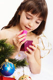 Little smiling girl opening christmas present. By a Christmas tree Royalty Free Stock Photos