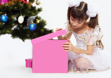 Little smiling girl opening christmas present. By a Christmas tree Royalty Free Stock Image