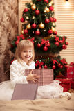 Little smiling girl opens a magic Christmas gift box Royalty Free Stock Image