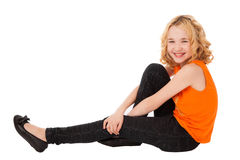 Little smiling girl in orange clothes and black shoes sitting Royalty Free Stock Photography