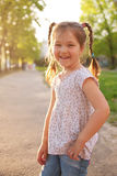 Little smiling girl with pigtails  in the sunlight. Stock Photo