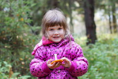 Little smiling girl in pink holds mushroom and looks Stock Image