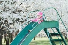 Little smiling girl in pink jacket sliding down old playground slide at fruit tree white blossom background Stock Images