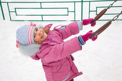 Little smiling girl on playground in winter Royalty Free Stock Images