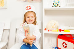 Little smiling girl playing dentist at the cabinet stock photos