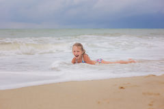 Little smiling girl playing on ocean waves on the beach royalty free stock photo