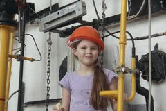 A little smiling girl is playing with red construction helmet Stock Image