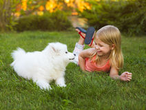Little smiling girl playing with Samoyed puppy in the summer gar Stock Photo