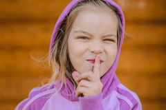 Little smiling girl in puts forefinger to lips Royalty Free Stock Images