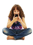 Little smiling girl reading sms on your cell phone Stock Image