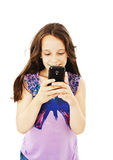Little smiling girl reading sms on your cell phone Royalty Free Stock Photo