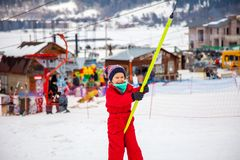 Little girl in red overall using button lift in ski resort in Bakuriani, Georgia royalty free stock photo